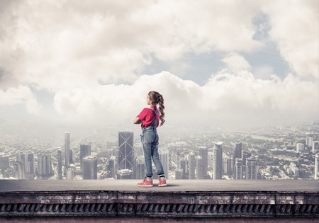 Cute kid girl standing on building roof with hands crossed on chest Stock Photo