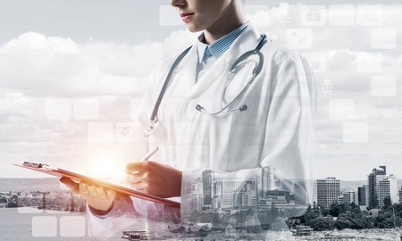 Side view of confident female doctor in white sterile coat making notes in notebook while standing outdoors with city view and medical interface icons on background. Medical industry. Double exposure Stock Photo