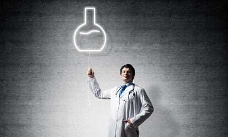 Young confident doctor in white medical uniform interracting with glowing vial symbol whie standing against dark gray wall on background. Stock Photo
