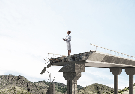 Conceptual image of woman doctor in white sterile suit standing on edge of broken bridge with landscape view on background. Medical industry concept