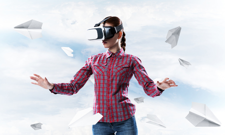 Young caucasian woman in virtual reality helmet against sky background Stock Photo