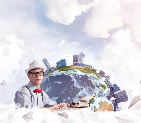Man writer in hat and bow-tie using typing machine while sitting at the table with flying paper planes and Earth globe among cloudy skyscape on background.