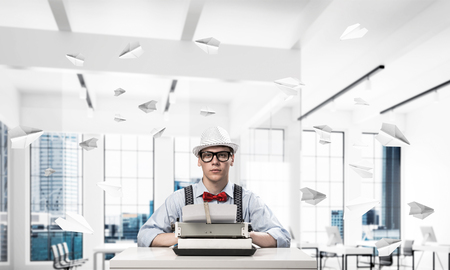 Young man writer in hat and eyeglasses using typing machine while sitting at the table indoors among flying paper planes and with office view on background. Stock Photo