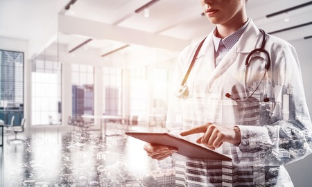Young female doctor in white sterile coat touching tablet screen while standing at hospital building. Digital technologies for medical employee. Double exposure Stockfoto