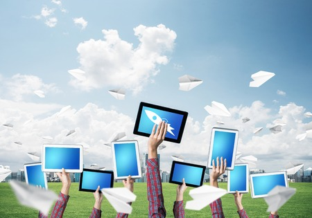 Set of tablets in female hands against nature background and paper planes in air