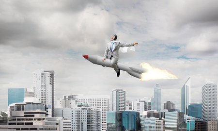 Conceptual image of young and happy businessman in suit flying on rocket with modern cityscape with skyscrapers and blue sky on background. Stock Photo