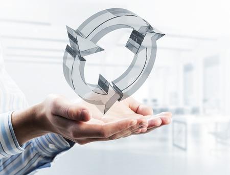 Cerca del empresario sosteniendo en la palma de la mano recarga el icono de vidrio. Técnica mixta Foto de archivo