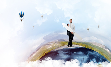 Conceptual image of young successful business man in suit pointing aside by means of big white banner in form of arrow while standing on Earth globe.