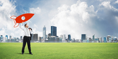 Horizontal shot of successful and young businessman standing on green lawn and throwing huge rocket in the air with modern city view on background Imagens
