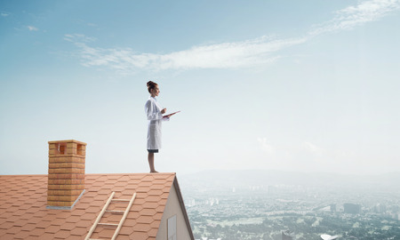 Horizontal shot of young female doctor in white medical suit holding notebook in hands while standing at the top building on brick roof with cloudy sky and cityscape view on background.