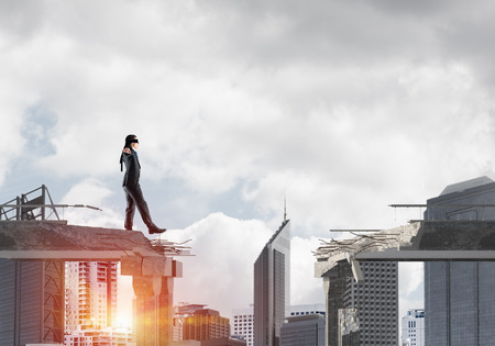 Businessman walking blindfolded on concrete bridge with huge gap as symbol of hidden threats and risks. Cityscape view with sunlight on background. 3D rendering. Standard-Bild