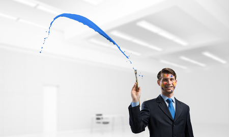 Horizontal shot of cheerful and young businessman in black suit gesturing and smiling while standing near blue liquid splash inside bright modern office.