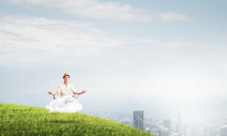 Young man in white clothing keeping eyes closed and looking concentrated while meditating on cloud in the air with city view on background.