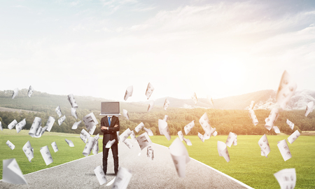 Businessman in suit with laptop instead of head keeping arms crossed while standing on the road among flying papers with beautiful landscape on background.