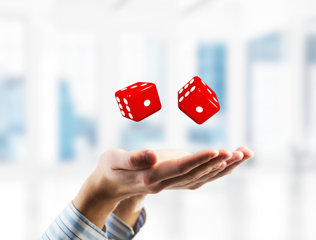Close of businessman hands with dice as game concept. Mixed media