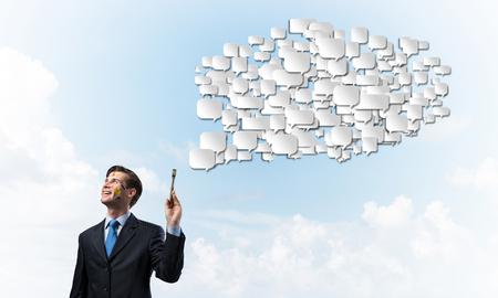 Imagen conceptual del hombre de negocios joven y exitoso en traje negro sosteniendo el pincel en la mano y sonriendo mientras está de pie con la nube charlando contra el cielo nublado en el fondo.