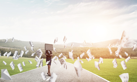 Business woman in suit with TV instead of head keeping arms crossed while standing on the road among flying papers with beautiful landscape on background.
