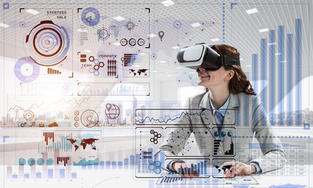 Beautiful and young business woman in suit using virtual reality headset with digital media structure while standing inside bright office. Up to date technologies