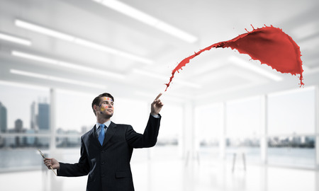 Young and successful businessman in black suit holding paintbrush in hand and smiling while standing with colourful liquid splash inside modern bright office.