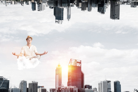 Young man keeping eyes closed and looking concentrated while meditating on cloud in the air between two urban worlds.
