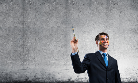 Horizontal shot of young businessman in suit holding paintbrush in hand and smiling while standing against dark gray wall on background 스톡 콘텐츠