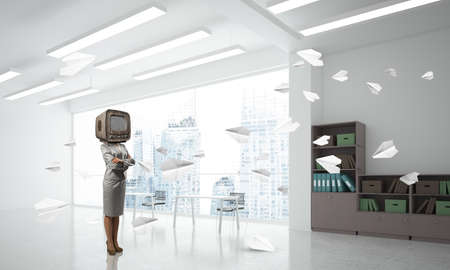 Business woman in suit with an old TV instead of head keeping arms crossed while standing among flying paper planes inside office building. 3D rendering.