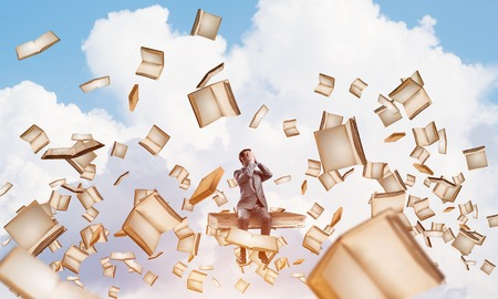 Young shocked businessman sitting on pile of books and covering eyes with palms