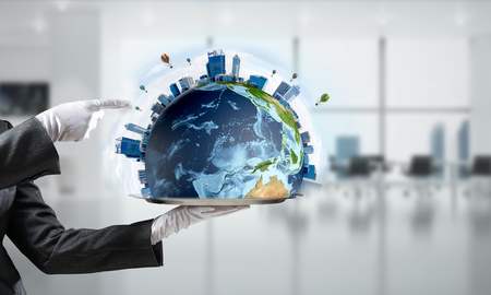 Cropped image of waitresss hand in white glove presenting Earth globe with buildings on metal tray with office view on background. 3D rendering.