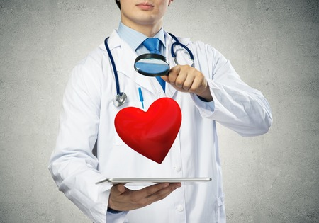 Conceptual image of professional doctor in white medical uniform is studying red heart symbol through magnifier while standing against gray background Stock Photo
