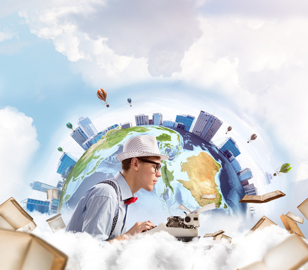 Side view of hard-working man writer using typing machine while sitting at the table with flying books and Earth globe among cloudy skyscape on background. Stock Photo