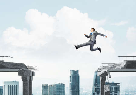 Businessman jumping over gap in concrete bridge as symbol of overcoming challenges. Cityscape on background. 3D rendering. Фото со стока
