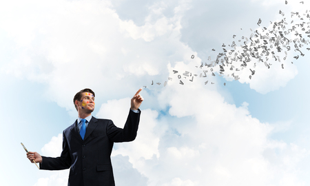Successful and confident businessman keeping paintbrush in his hand while standing with flying letters against cloudy skyscape on background.