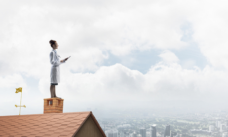 Horizontal shot of young woman doctor in white uniform standing at the top of brick roof and using tablet, skyscape and city view on background. Medical industry concept Banque d'images