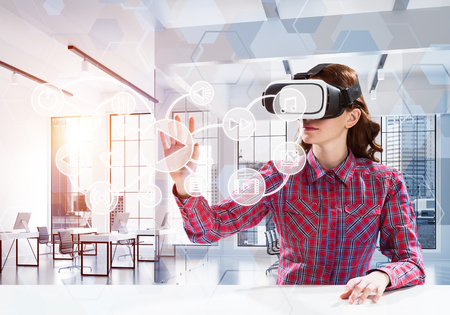 Conceptual image of young woman in checkered shirt using virtual reality headset with media interface while sitting inside bright building. Up to date technologies for education Stock Photo