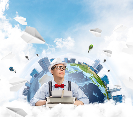 Portrait of handsome  writer in bow-tie and hat looking away while working with typing machine at the table with flying paper planes and Earth globe among cloudy skyscape