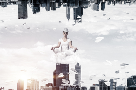 Young woman keeping eyes closed and looking concentrated while meditating on cloud among flying paper planes and between two urban worlds.