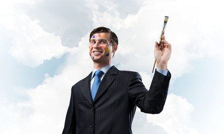 Happy and young businessman in black suit holding paintbrush in his hand and smiling while standing against blue cloudy skyscape view on background.