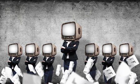 Business women in suits with old TV instead of their heads keeping arms crossed while standing in a row among flying papers in empty room with gray wall on background. Stock fotó