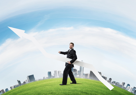 Conceptual image of young successful business man in black suit pointing aside by means of big white banner in form of arrow while standing on green meadow with city on background. Banco de Imagens - 112305847