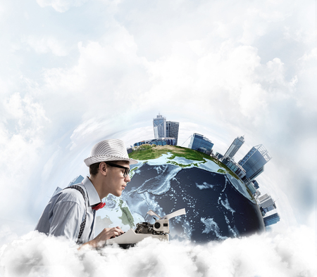 Side view of hard-working man writer using typing machine while sitting at the table with panoramic Earth view and cloudy skyscape on background.