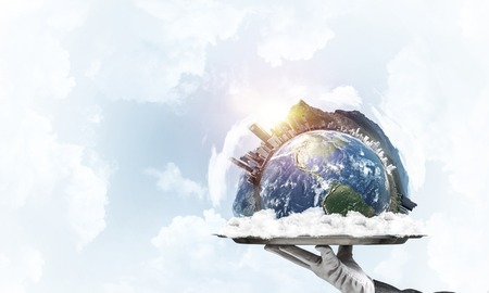 Cropped image of waitress's hand in white glove presenting Earth globe on metal tray with cloudy skyscape on background. Imagens