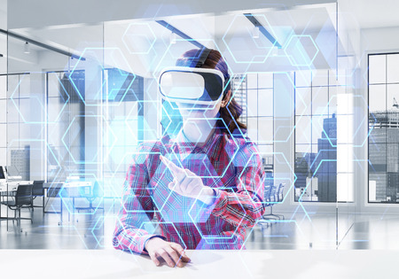 Beautiful and young woman in red checkered shirt using VR goggles and interracting with digital media interface while sitting inside bright office building. Virtual reality device
