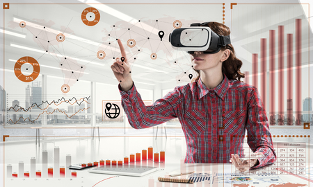 Young woman in checkered shirt using VR headset with digital media interface while sitting inside bright office building. Virtual reality technologies for education Stock Photo