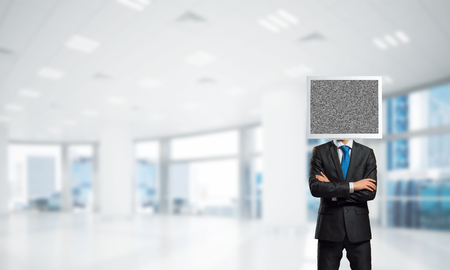 Cropped image of businessman in suit with monitor instead of head keeping arms crossed while standing inside office building. Stock fotó