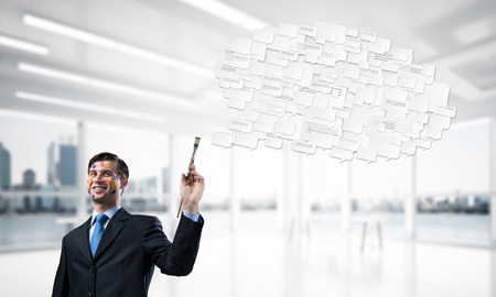 Conceptual image of young and successful businessman in black suit holding paintbrush in hand and smiling while standing with chatting cloud inside modern bright office.