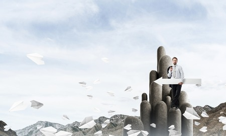 Conceptual image of young businessman in suit standing on high stone column and keeping big white arrow in hand with cloudy skyscape view on background