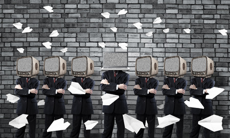 Businessmen in suits with old TV instead of their heads keeping arms crossed while standing in a row and one at the head with laptop in empty room against gray wall on background. Stockfoto - 112464531