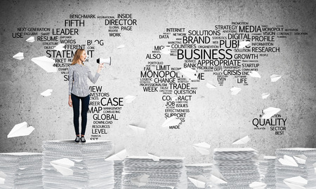 Woman in casual wear standing among flying paper planes with speaker in hand with business-related terms in form of world map on background. Mixed media.