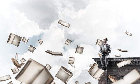 Funny man in red glasses and suit sitting on top and reading book