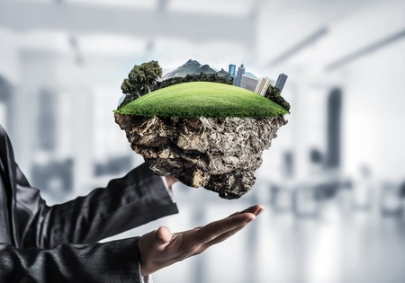 Business woman in suit keeping green island with landscape and city in her hands with office view on background. Mixed media. Stok Fotoğraf